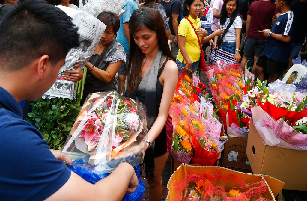 A couple buys a bouquet of flowers at a flower market on Valentine's eve Wednesday, February 13, 2019 in Manila, Philippines. (AP Photo/Bullit Marquez)