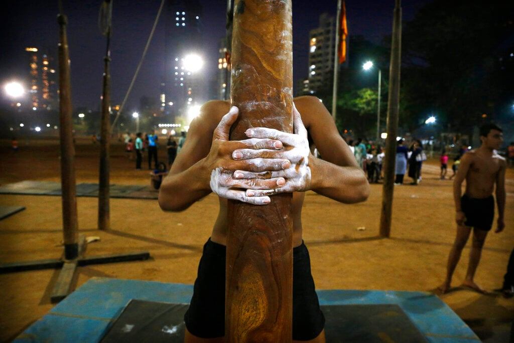 In this February 4, 2019, photo, a player tightens his grip on a mallakhamb pole as he trains at Shivaji Park in Mumbai, India. The word mallakhamb comes from malla, meaning wrestler, and khamb, or pole, and is a traditional training exercise for wrestlers in India. After centuries of being practiced in isolation in the subcontinent, mallakhamb is set to have its first international championship in Mumbai on February 16 and 17. (AP Photo/Rafiq Maqbool)
