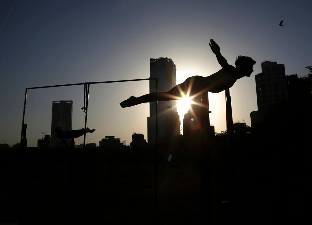 In this February 7, 2019, photo, a player performs on a Mallakhamb pole during an early morning training session at Shivaji Park in Mumbai, India. (AP Photo/Rafiq Maqbool)