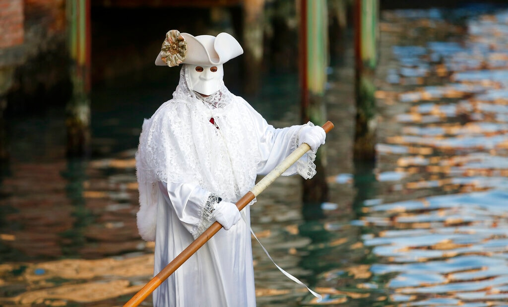 A masked man sails on a gondola as part of the Carnival in Venice, Italy, Saturday, February 16, 2019. (AP Photo/Antonio Calanni)