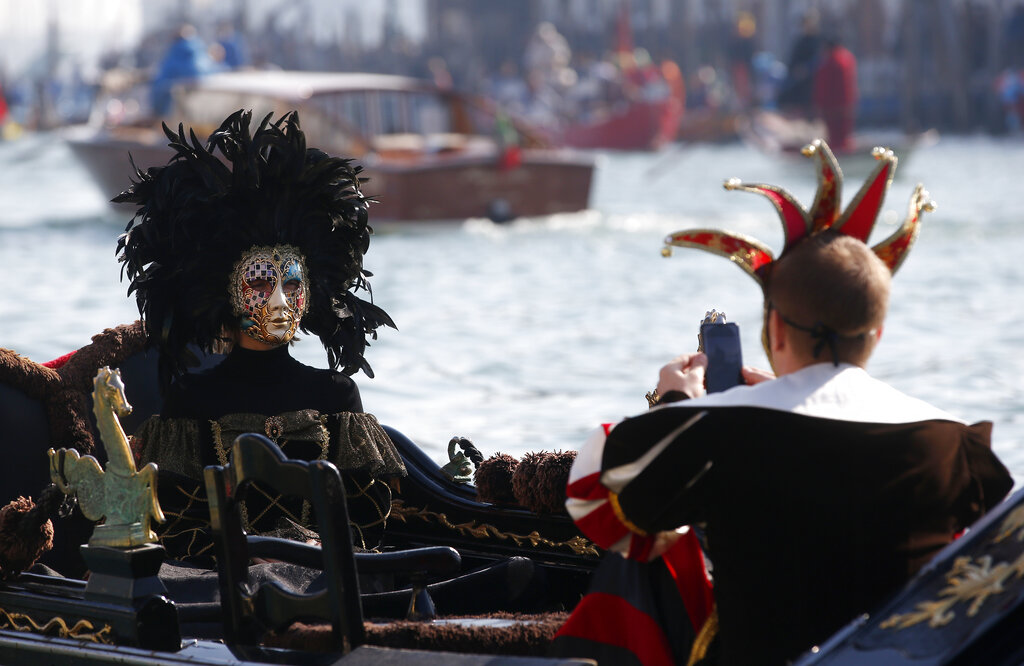 Masked people stand on a gondola during the water parade, part of the Venice Carnival, in Venice, Italy, Sunday, February 17, 2019. (AP Photo/Antonio Calanni)