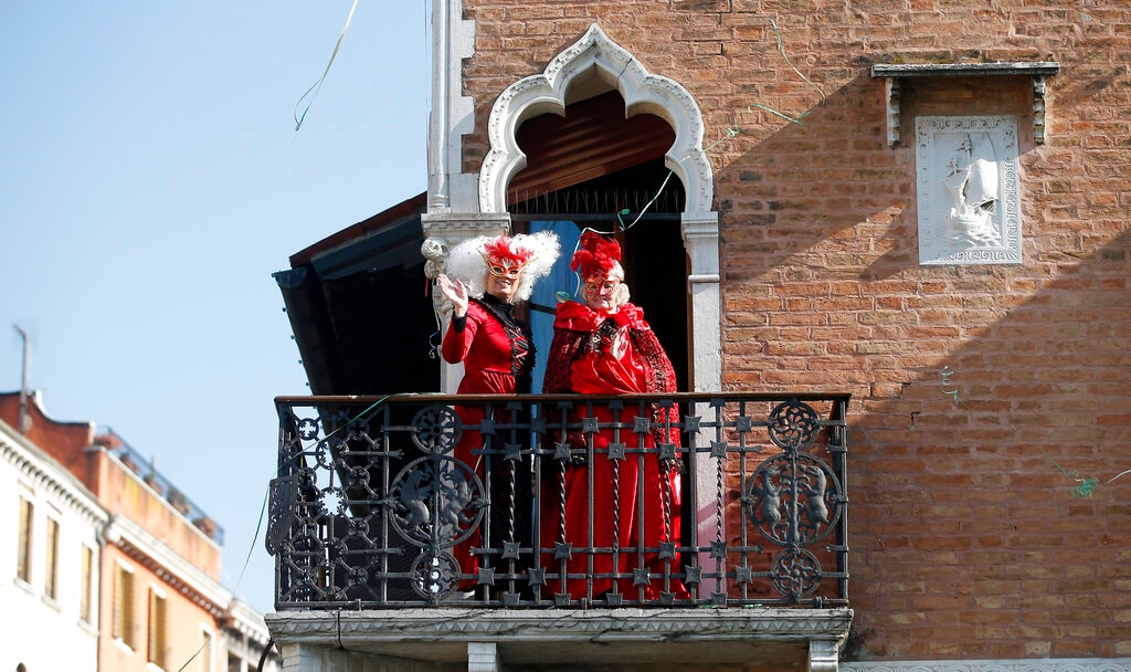 Masked women stand on a balcony during the water parade, part of the Venice Carnival, in Venice, Italy, Sunday, February 17, 2019. (AP Photo/Antonio Calanni)