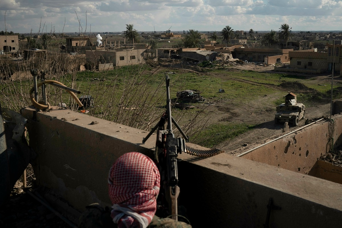 A US-backed Syrian Democratic Forces (SDF) fighter stands atop a building in  Baghouz. (AP Photo/Felipe Dana)