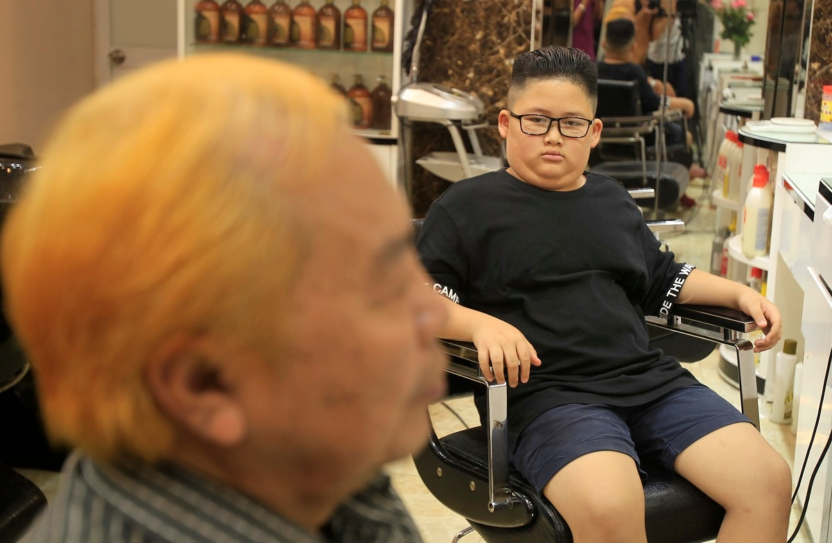 Le Phuc Hai, 66, left, and To Gia Huy, 9, sit after having Trump and Kim haircuts in Hanoi, Vietnam. US President Donald Trump and North Korean leader Kim Jong Un have become the latest style icons in Hanoi, a week before their second summit is to be held in the capital city of Vietnam. (AP Photo/Hau Dinh, File)