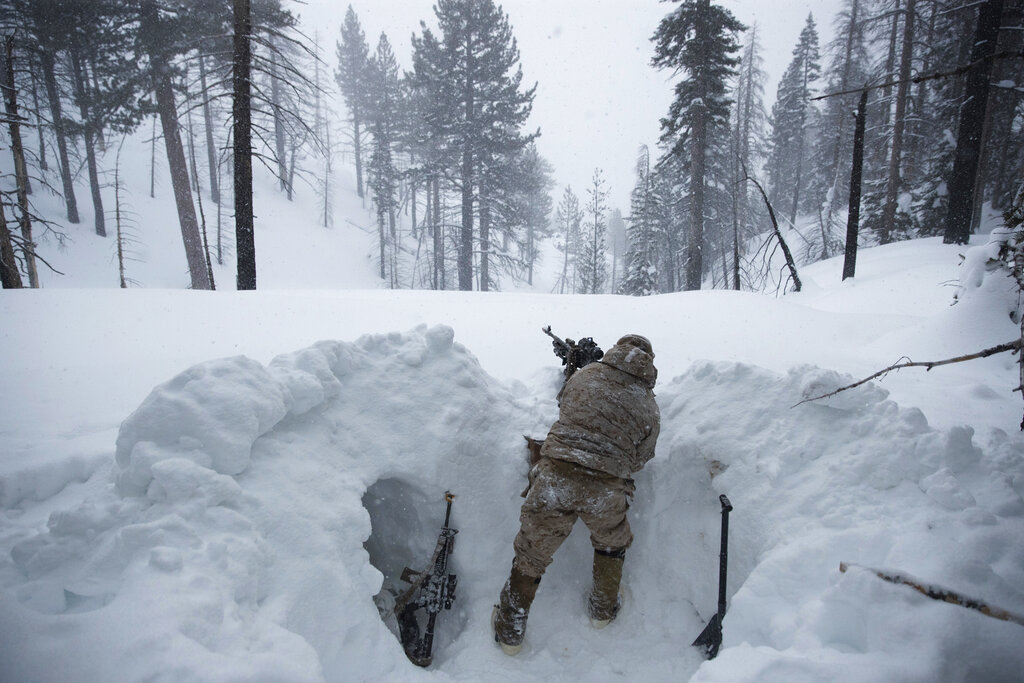 A US Marine covers a machine gun in a trench while preparing for advanced cold-weather training at the Marine Corps Mountain Warfare Training Center on Saturday, February 9, 2019, in Bridgeport, California. (AP)