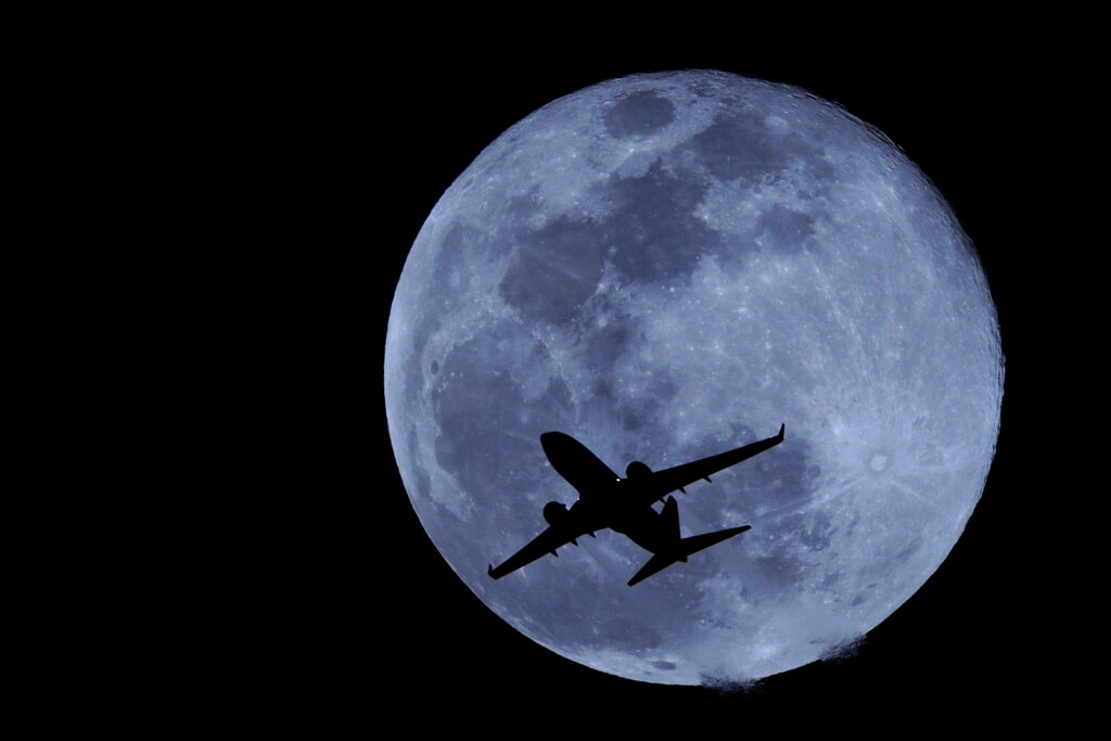 A passenger jet is silhouetted against the rising full moon as it takes off from Sky Harbor airport Tuesday, Feb. 19, 2019, in Phoenix. (AP)