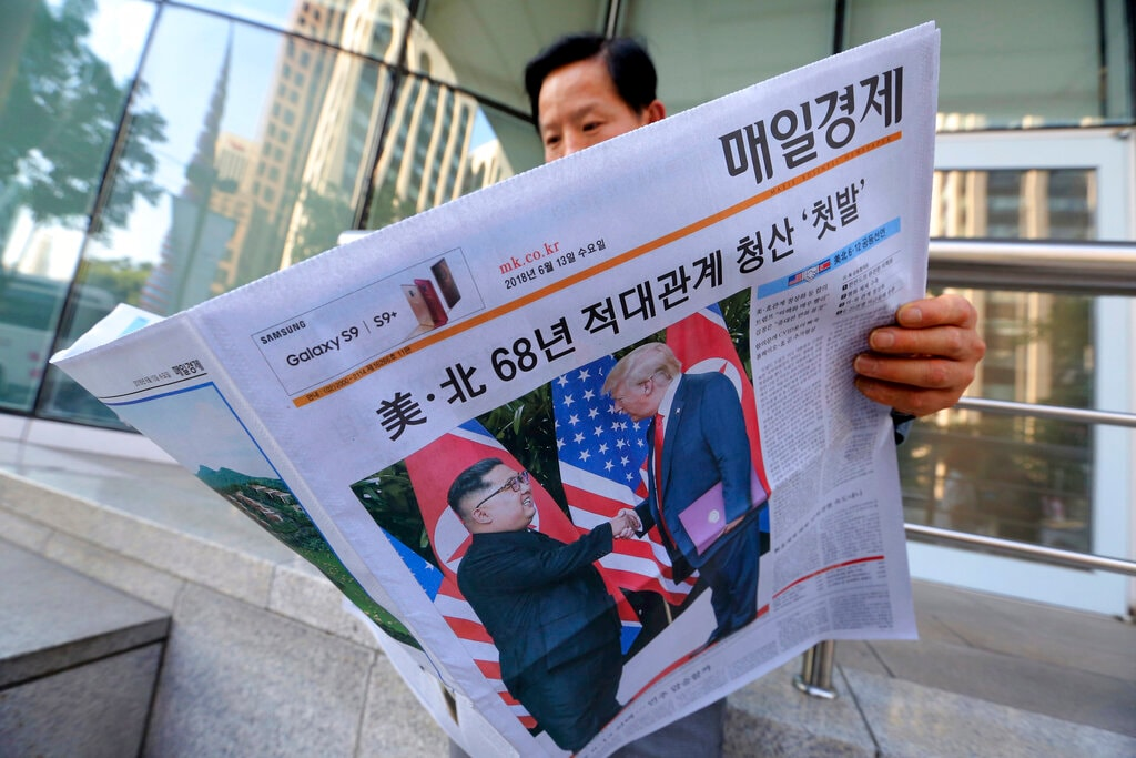 In this June 12, 2018, file photo, a man reads a newspaper reporting the summit between US President Donald Trump and North Korean leader Kim Jong Un, at a newspaper distributing station in Seoul, South Korea. (AP Photo/Ahn Young-joon, File)