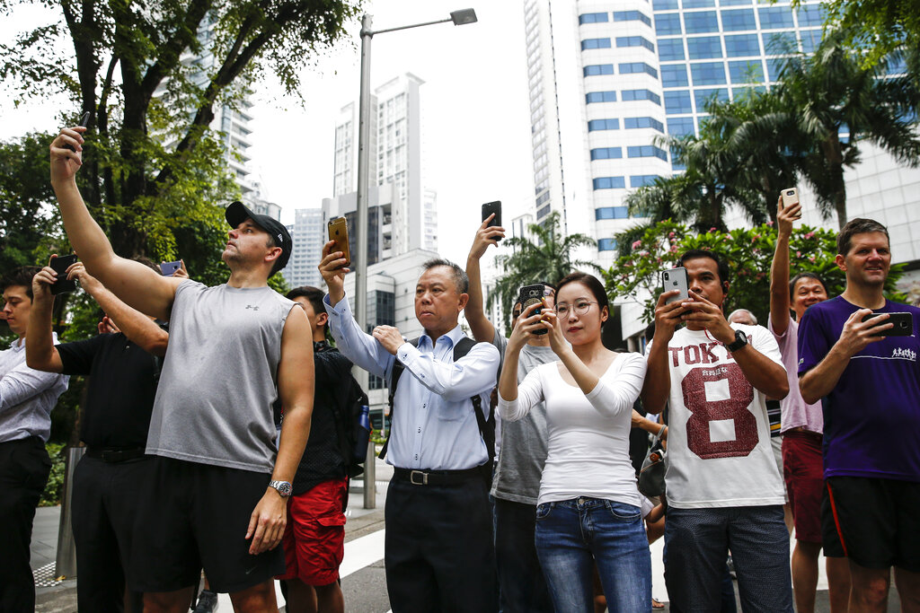 In this June 12, 2018, file photo, spectators take photos of the motorcade of North Korea leader Kim Jong Un as it leaves the St. Regis Hotel on the way to the Capella Hotel in Singapore where the summit between Kim and US President Donald Trump is scheduled. (AP Photo/Yong Teck Lim, File)