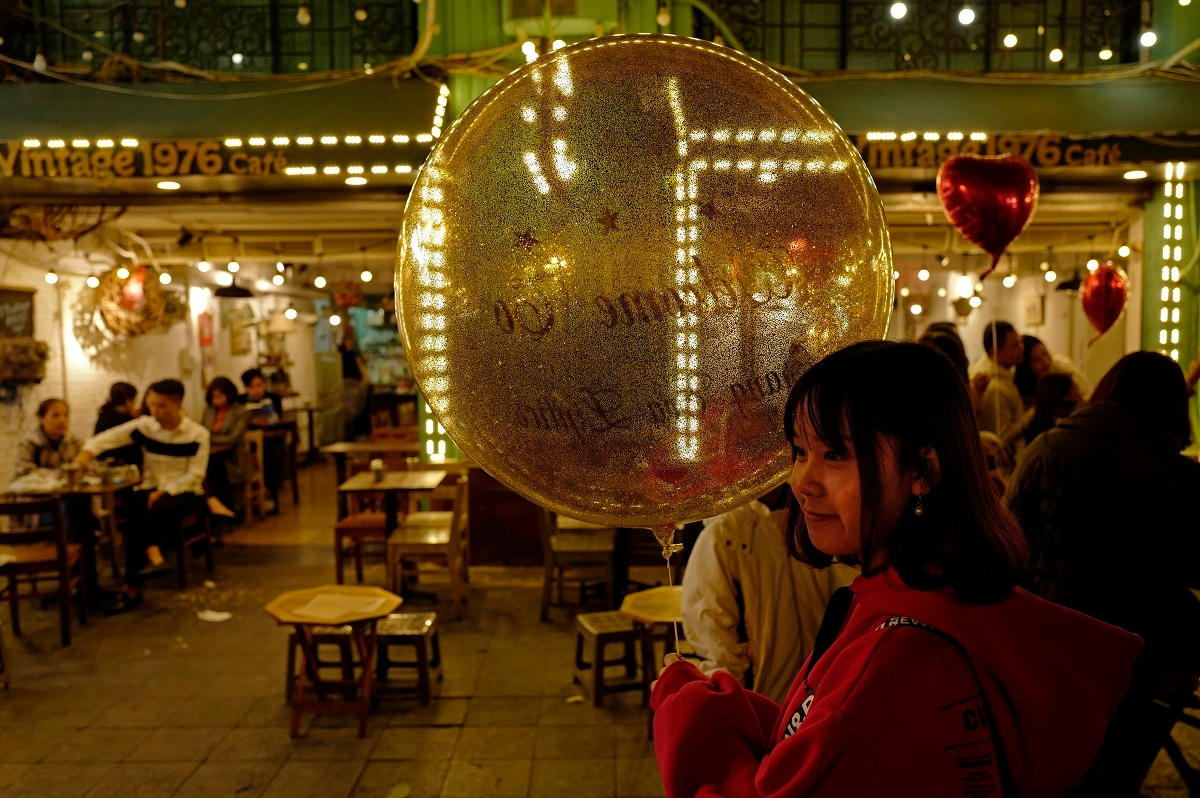 A girl poses for a photo with a big balloon near Hoan Kiem Lake in Hanoi, Vietnam. (AP Photo/Vincent Yu)