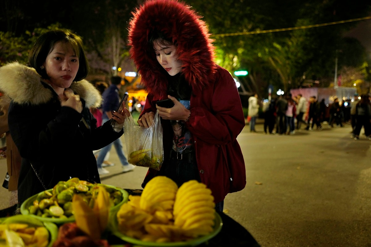 Women buy fruits at a booth near Hoan Kiem Lake in Hanoi, Vietnam. (AP Photo/Vincent Yu)