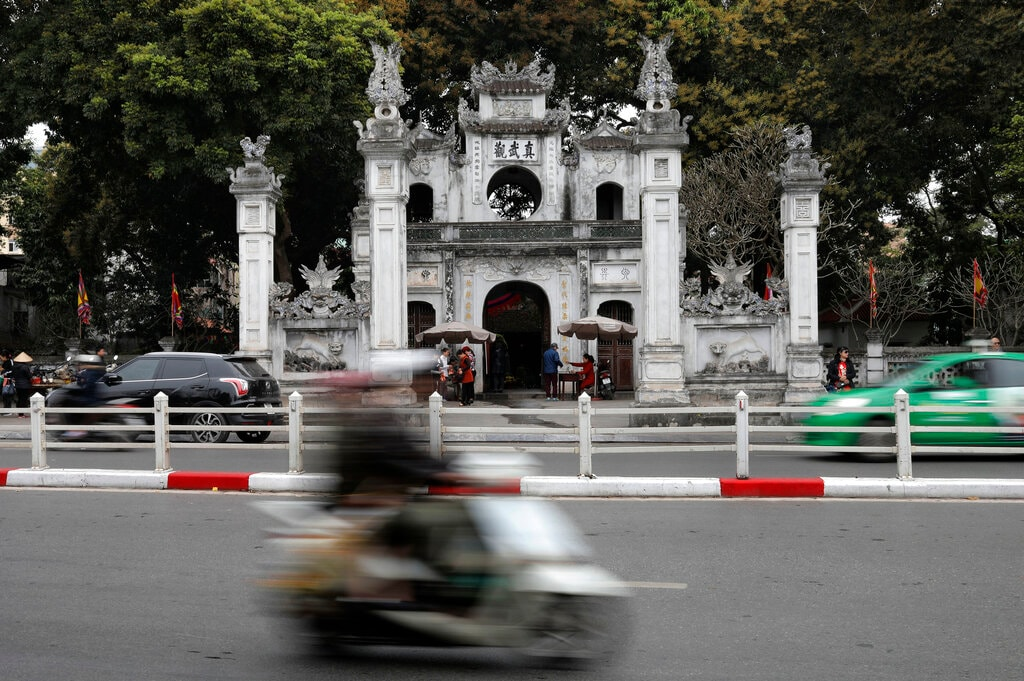 A motorist drives past the Quan Thanh Temple in Hanoi, Vietnam, Sunday, February 24, 2019. (AP Photo/Vincent Yu)
