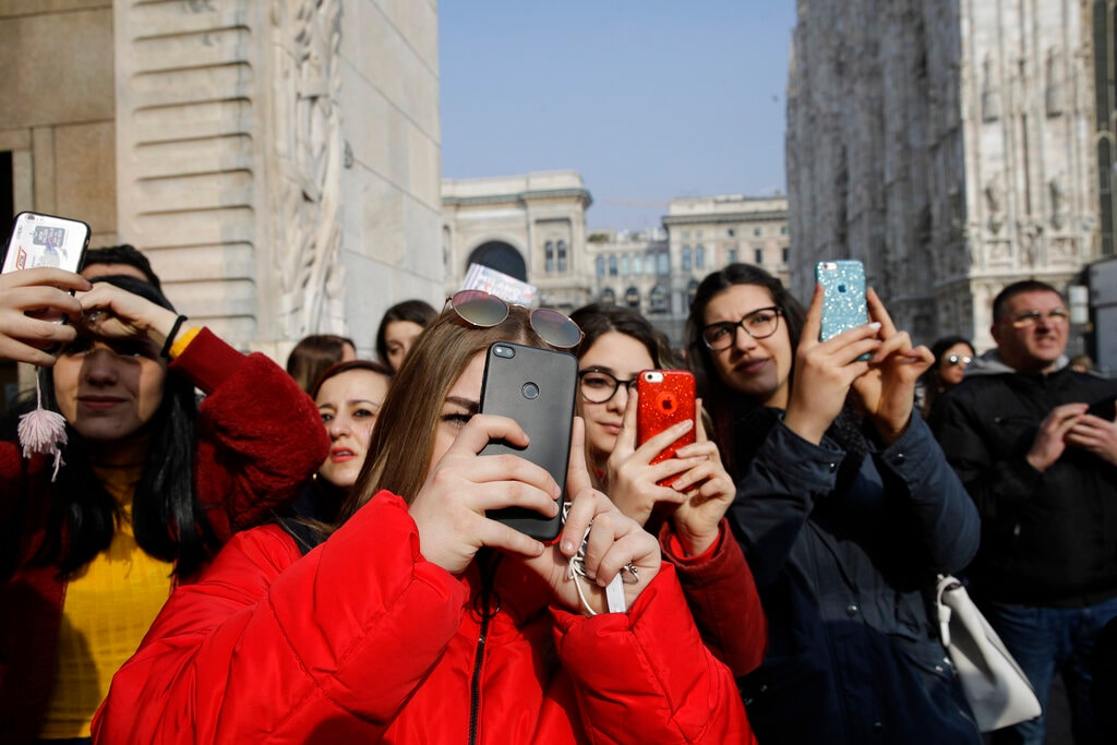In this picture taken on Tuesday, February 19, 2019, teenagers shoot video and photos to guests attending the Alberto Zambelli women's Fall-Winter 2019-2020 fashion show, that was presented in Milan, Italy. (AP Photo/Luca Bruno)