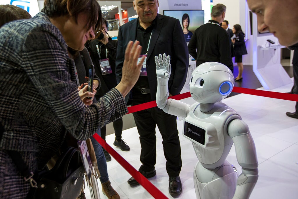 A XR-1 5G cloud robot by CloudMinds shakes hands with a visitor, during the Mobile World Congress wireless show, in Barcelona, Spain, Monday, Feb. 25, 2019. The annual Mobile World Congress (MWC) runs from 25-28 February in Barcelona, where companies from all over the world gather to share new products. (AP Photo/Emilio Morenatti)