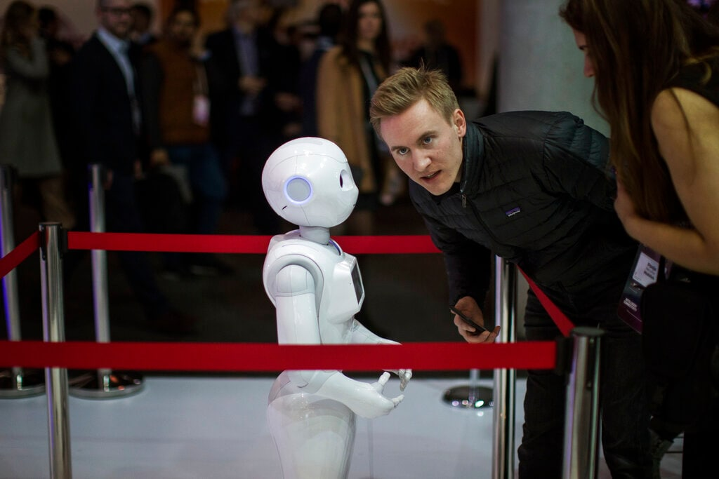 A XR-1 5G cloud robot by CloudMinds speaks with a visitor, during the Mobile World Congress wireless show, in Barcelona, Spain, Monday, Feb. 25, 2019. The annual Mobile World Congress (MWC) runs from 25-28 February in Barcelona, where companies from all over the world gather to share new products. (AP Photo/Emilio Morenatti)
