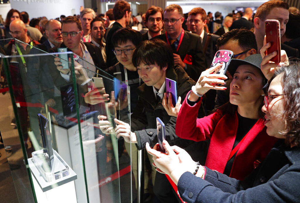 Attendees take pictures of the new Huawei Mate X foldable 5G smartphone during the Mobile World Congress wireless show, in Barcelona, Spain, Monday, Feb. 25, 2019. The annual Mobile World Congress (MWC) runs from 25-28 February in Barcelona, where companies from all over the world gather to share new products. (AP Photo/Manu Fernandez)