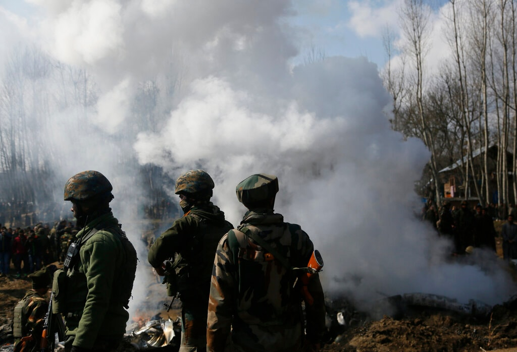 Indian army soldiers stand near the wreckage of an Indian aircraft after it crashed in Budgam area, outskirts of Srinagar, Kashmir, Wednesday, February 27, 2019. (AP Photo/Mukhtar Khan)