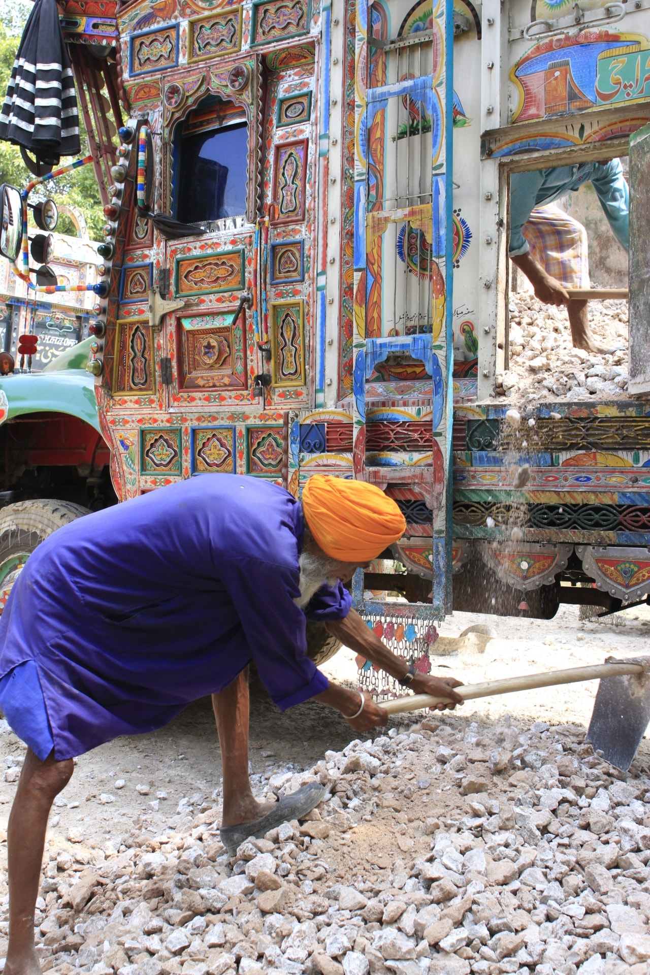 An Indian porter collects gypsum offloaded by Pakistani trucks to take them to Indian lorries.