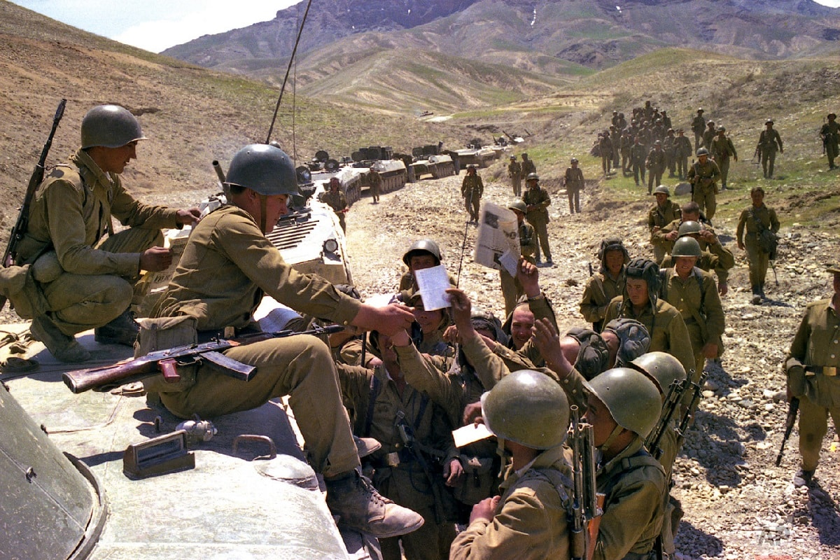 In this undated photo, Soviet soldiers get fresh newspapers and mail while a convoy stopped somewhere in Afghanistan. (Leonid Yakutin/Defense Ministry Press Service via AP)