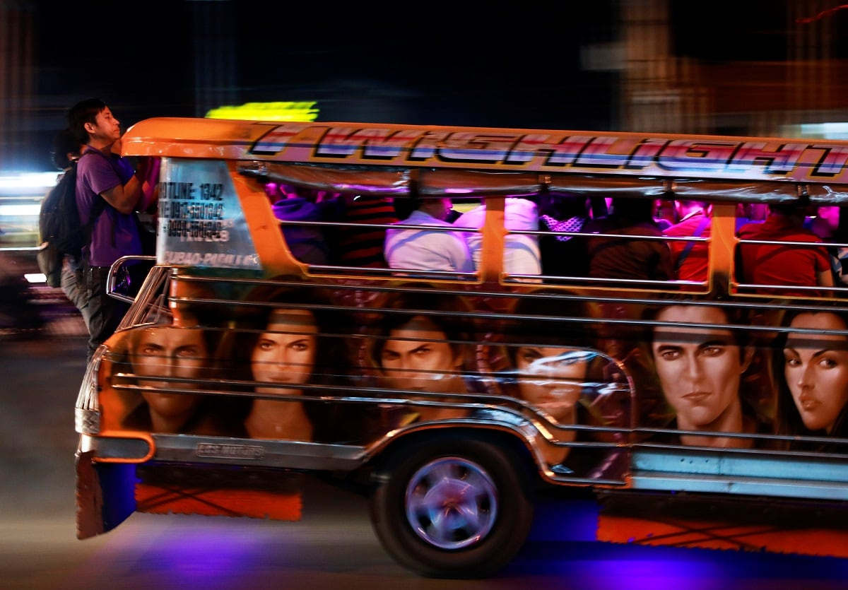 Commuters hang on to the back of a crowded jeepney in Cainta, Rizal, Philippines. (REUTERS/Eloisa Lopez)