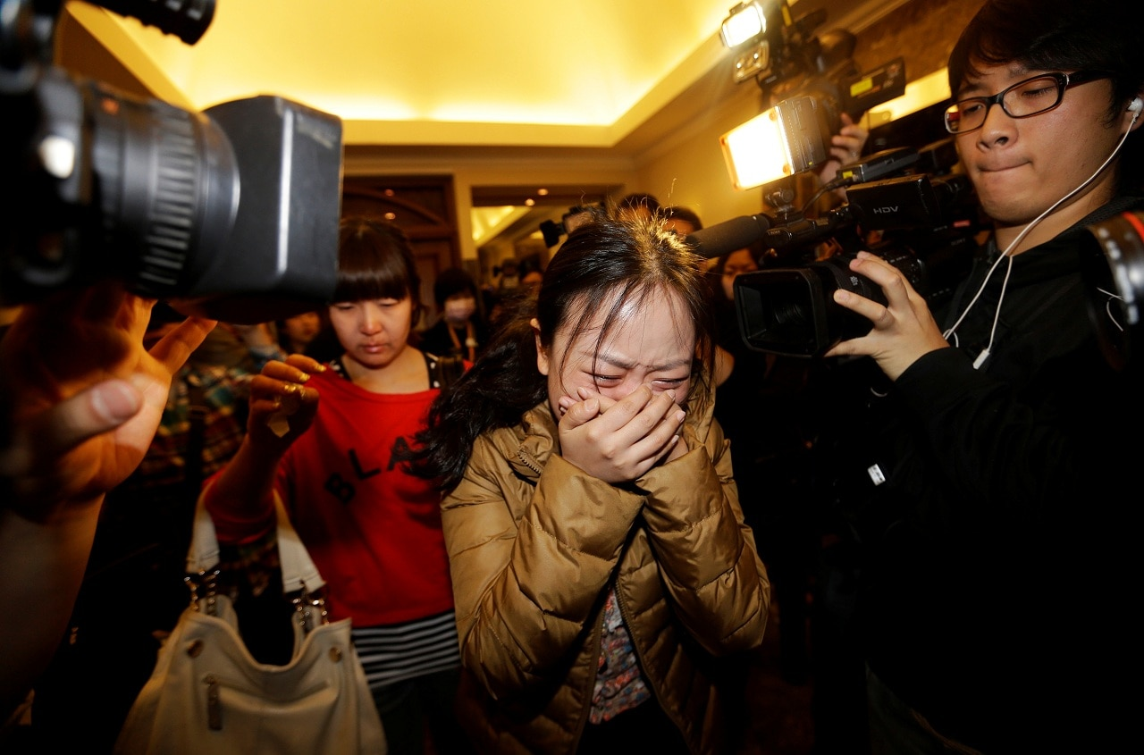 A relative (front) of a passenger of Malaysia Airlines flight MH370 cries as she walks past journalists at a hotel in Beijing March 9, 2014. (File photo: Reuters)