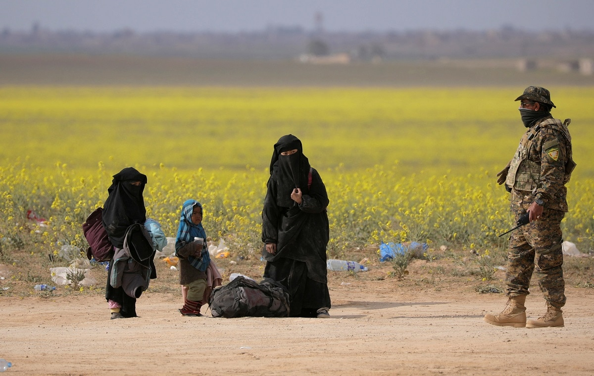A woman stands with her belongings near Baghouz, Deir Al Zor province, Syria. (REUTERS/ Rodi Said)