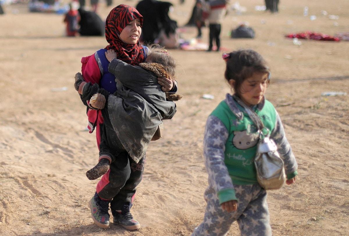 A girl walks as she holds a child near Baghouz, Deir Al Zor province. (REUTERS/ Rodi Said)