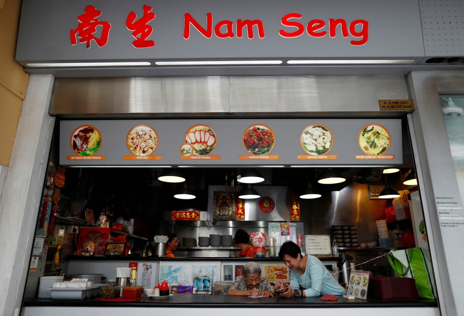 Hawker Leong Yuet Meng, 90, of Nam Seng Noodle House, discusses with a friend about what lottery numbers to buy at her shop in Singapore February 22, 2019. REUTERS/Edgar Su