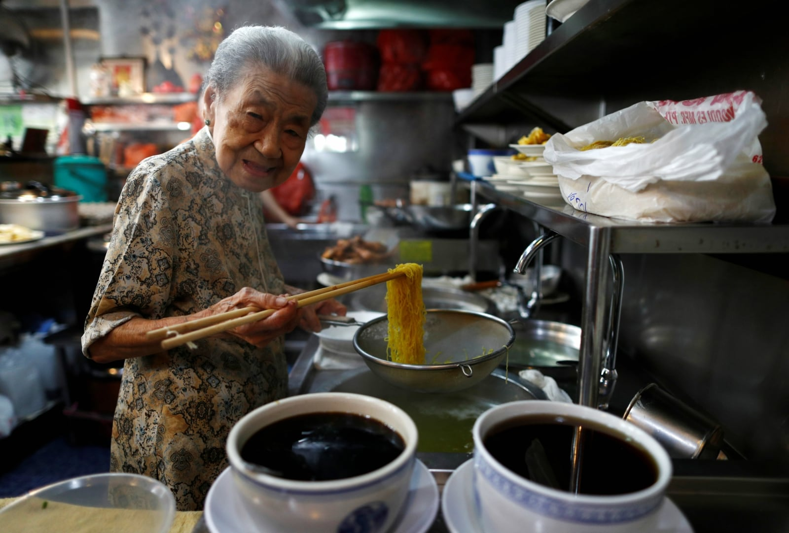 Hawker Leong Yuet Meng, 90, of Nam Seng Noodle House, poses as she cooks noodles at her shop in Singapore February 22, 2019. REUTERS/Edgar Su