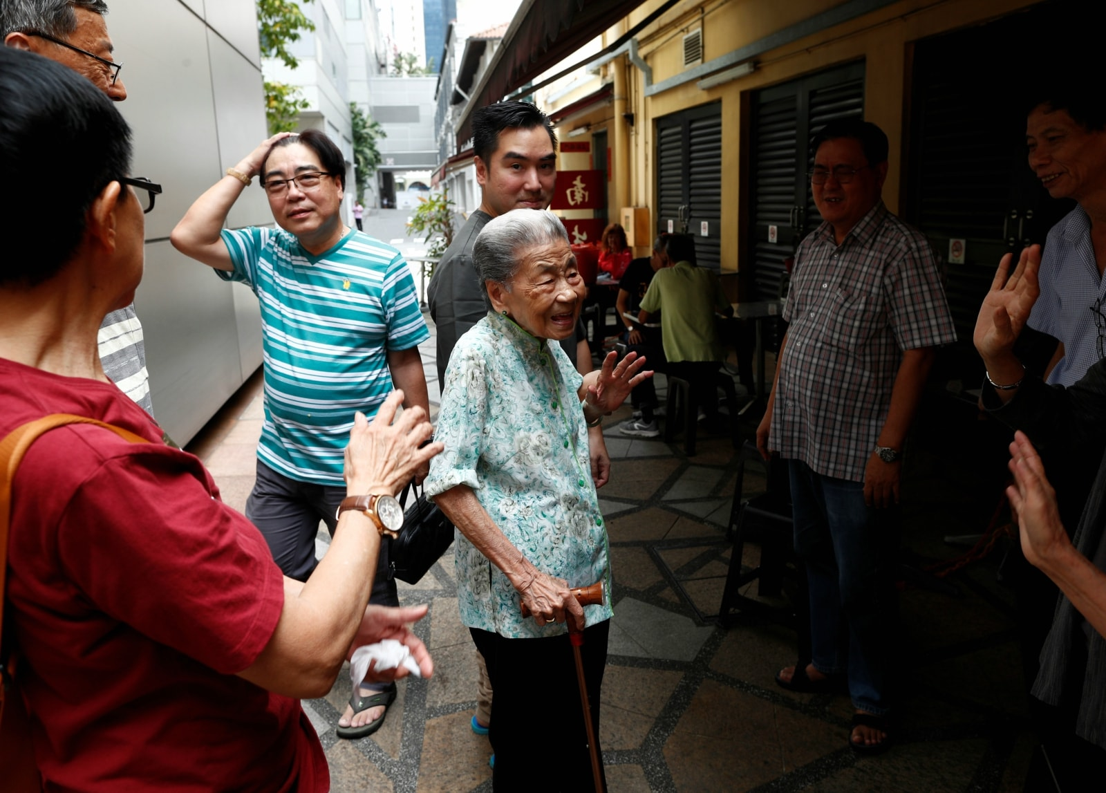Hawker Leong Yuet Meng, 90, of Nam Seng Noodle House, is greeted by longtime patrons and family friends outside her shop in Singapore February 16, 2019. REUTERS/Edgar Su
