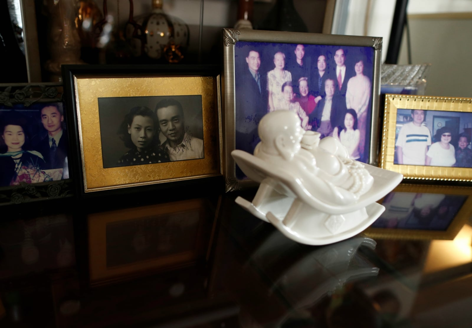 A black and white photo of hawker Leong Yuet Meng in her youth is pictured among her family photos at her home in Singapore on February 16, 2019. REUTERS/Edgar Su