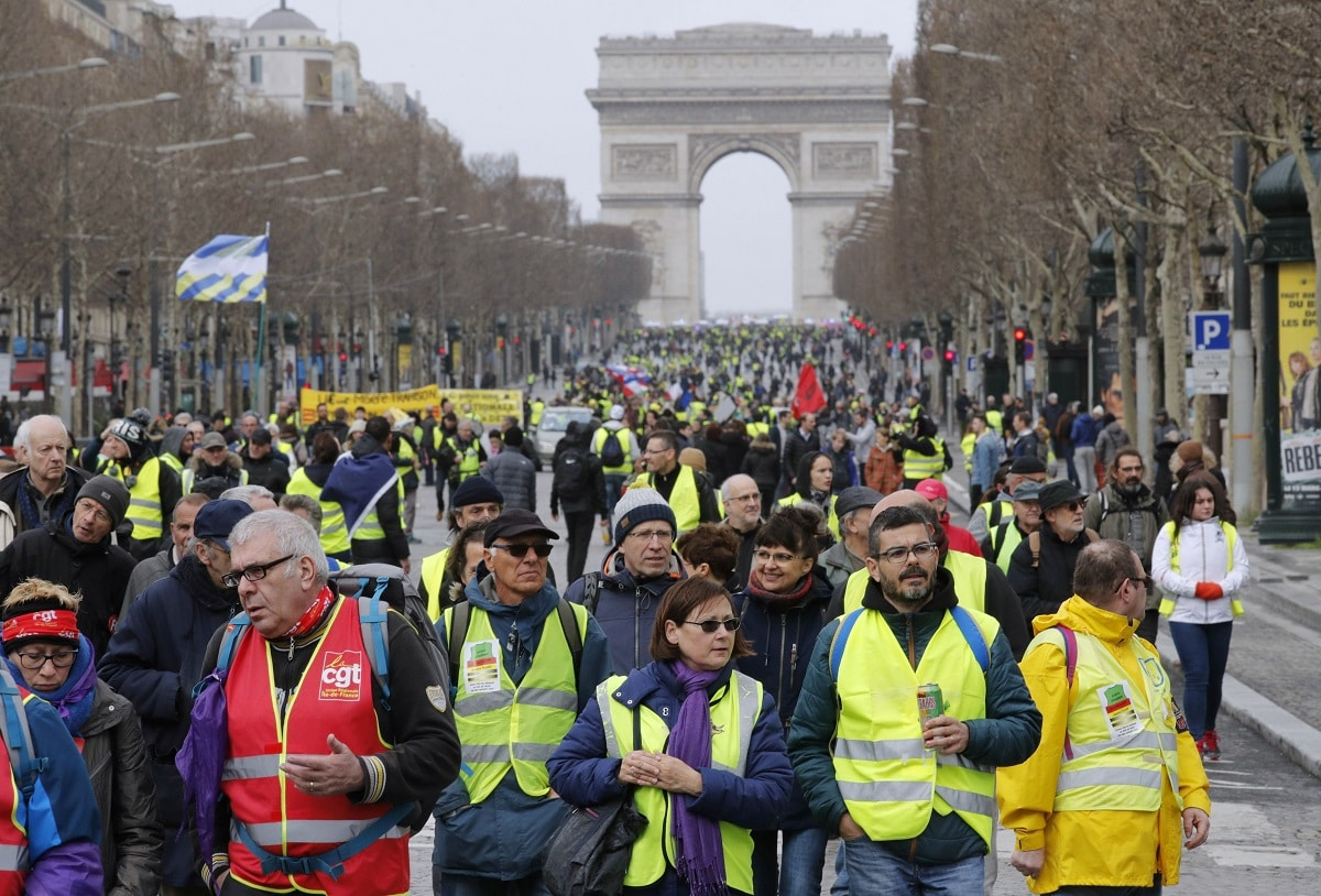 Protesters wearing yellow vests walk down the Champs Elysees during a demonstration by the