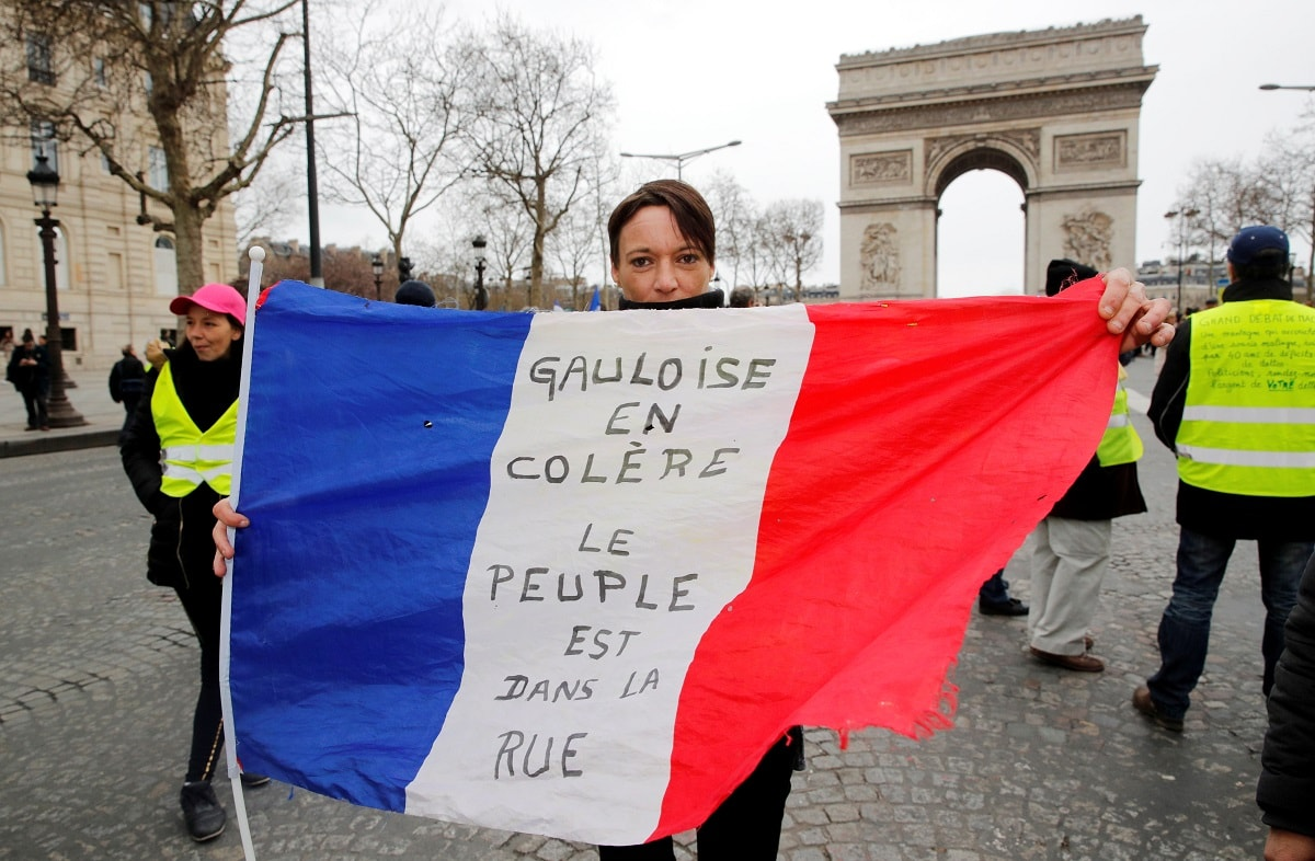 A protester holds the French flag on the Champs Elysees near the Arc de Triomphe during a demonstration by the