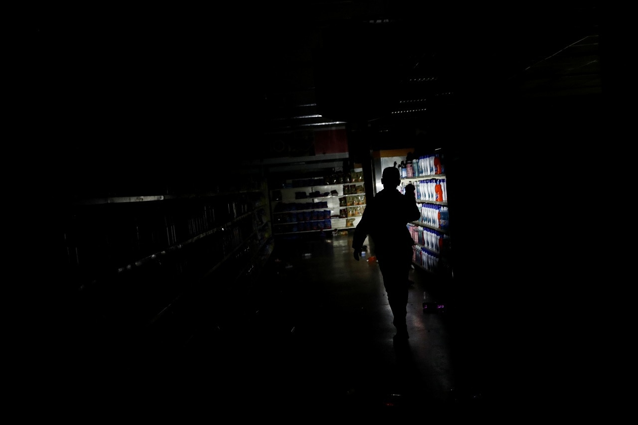 A worker inspects damage in a supermarket after it was looted during an ongoing blackout in Caracas, Venezuela March 10, 2019. (Reuters)