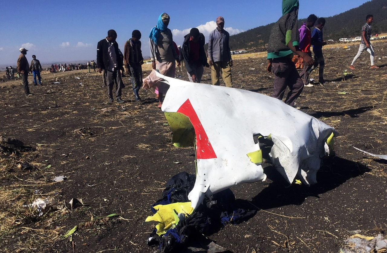 People walk past a part of the wreckage at the scene of the Ethiopian Airlines Flight ET 302 plane crash, near the town of Bishoftu, southeast of Addis Ababa, Ethiopia March 10, 2019. (Reuters)