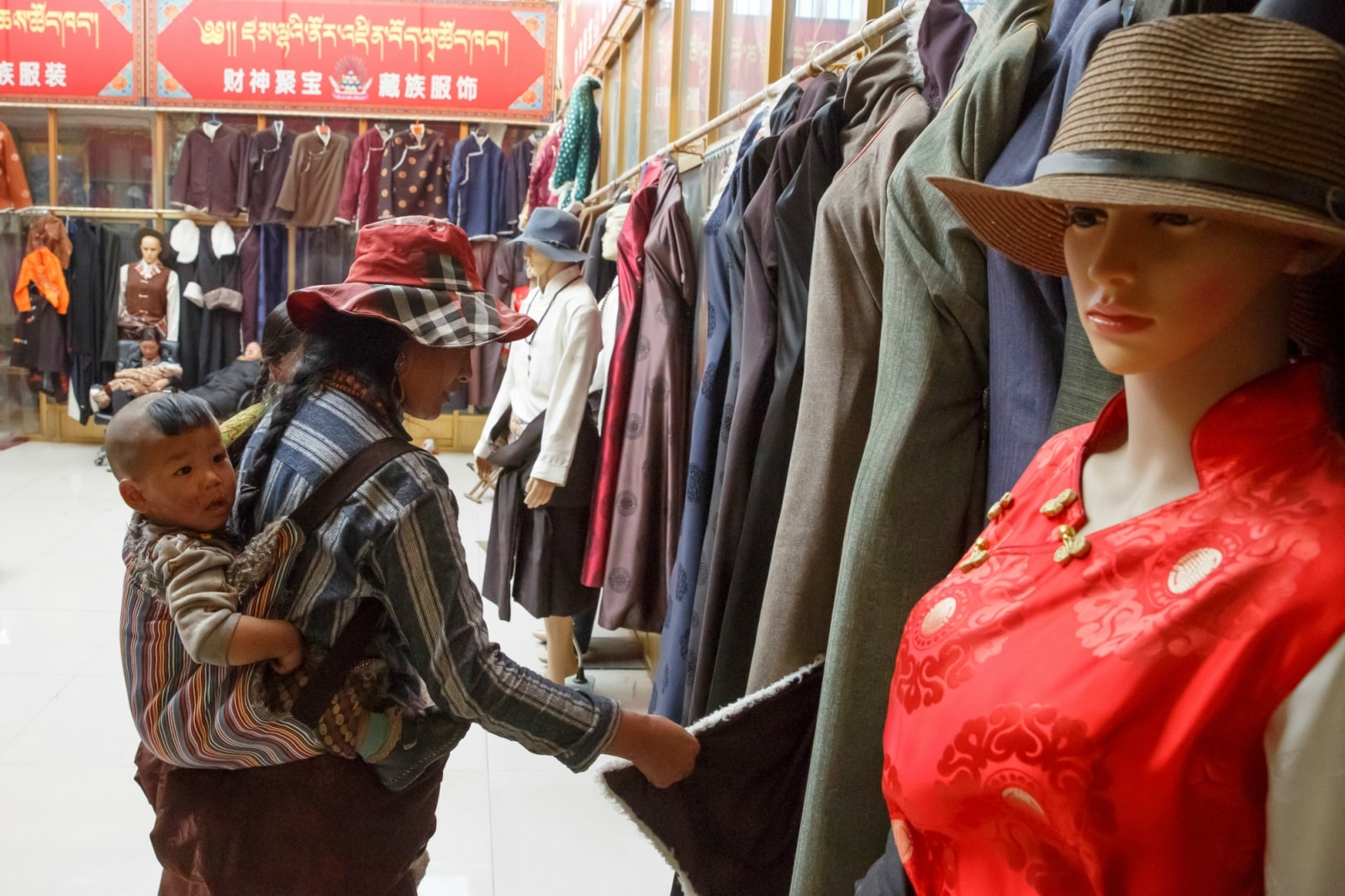A Tibetan woman carrying a child looks at clothes in a shop in the largely ethnic Tibetan town of Rebkong, Qinghai province, China March 9, 2019. REUTERS/Thomas Peter