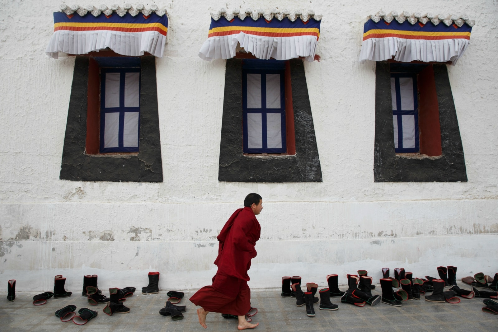 A Buddhist monk arrives late for a prayer session at Rongwo Monastery in the largely ethnic Tibetan town of Rebkong, Qinghai province, China March 9, 2019. REUTERS/Thomas Peter