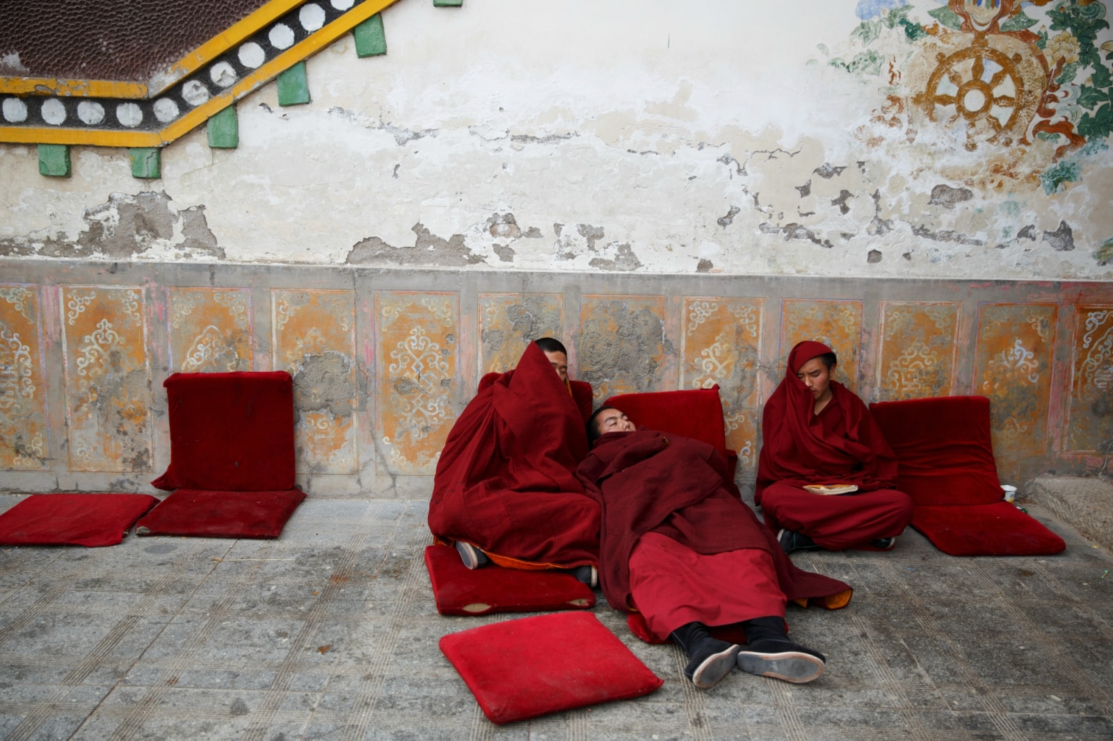 Buddhist monks rest outside a prayer hall between chanting sessions at Rongwo Monastery in the largely ethnic Tibetan town of Rebkong, Qinghai province, China March 9, 2019. REUTERS/Thomas Peter