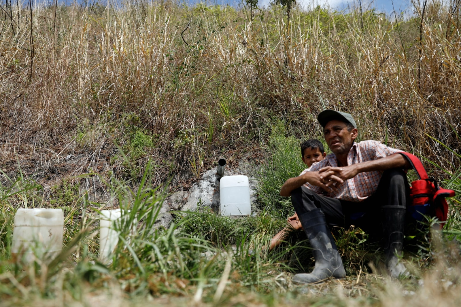 People wait as a bottle fills with water from a mountain stream in Caracas, Venezuela March 13, 2019. REUTERS/Carlos Jasso