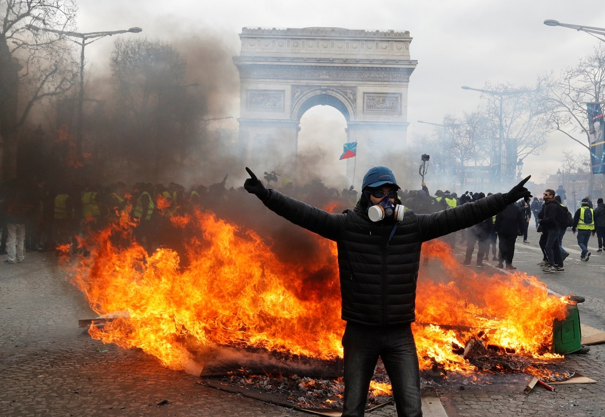 A protester stands in front of burning barricade during a demonstration by the