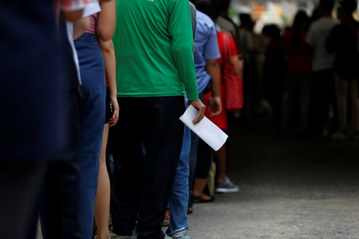 People line up for their early vote of the upcoming Thai election at a polling station in Bangkok, Thailand. (REUTERS/Soe Zeya Tun)