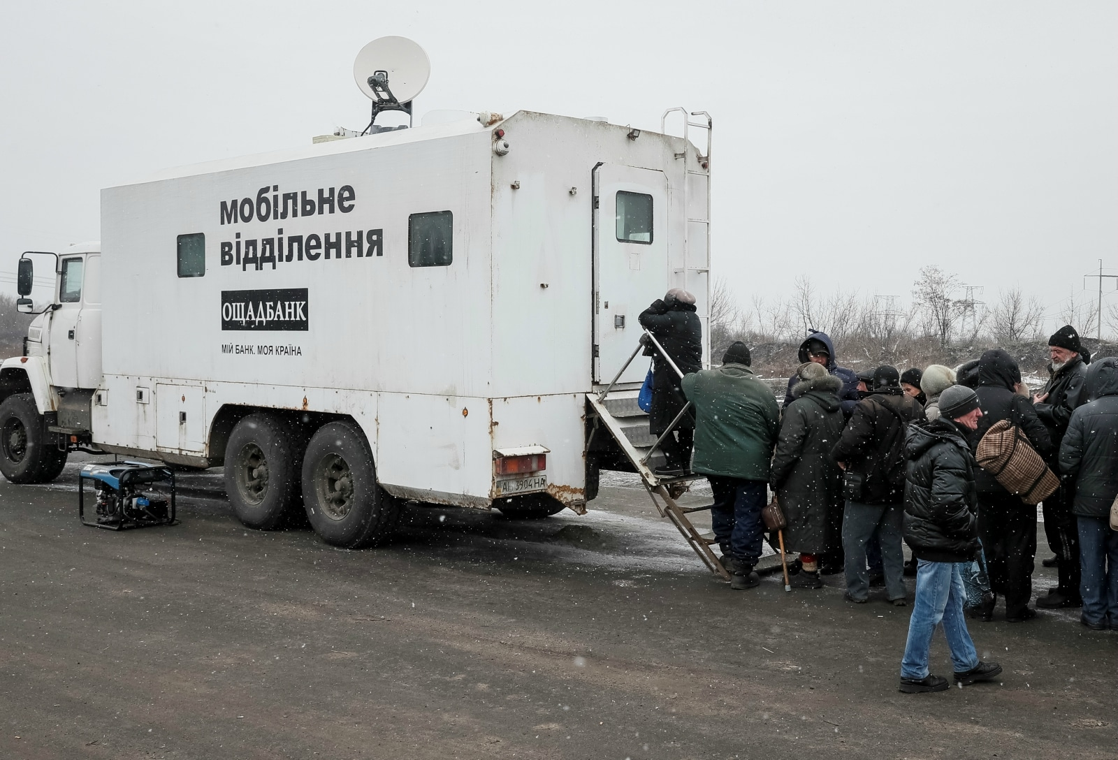 Local residents stand in line to an ATM located in an armoured truck after crossing the contact line between pro-Russian rebels and Ukrainian troops near the front line in Mayorsk, Ukraine, February 25, 2019. Employees from the state-run Oschadbank travel by armoured truck to a nearby checkpoint, to allow residents on both sides of the conflict to withdraw money. REUTERS/Gleb Garanich