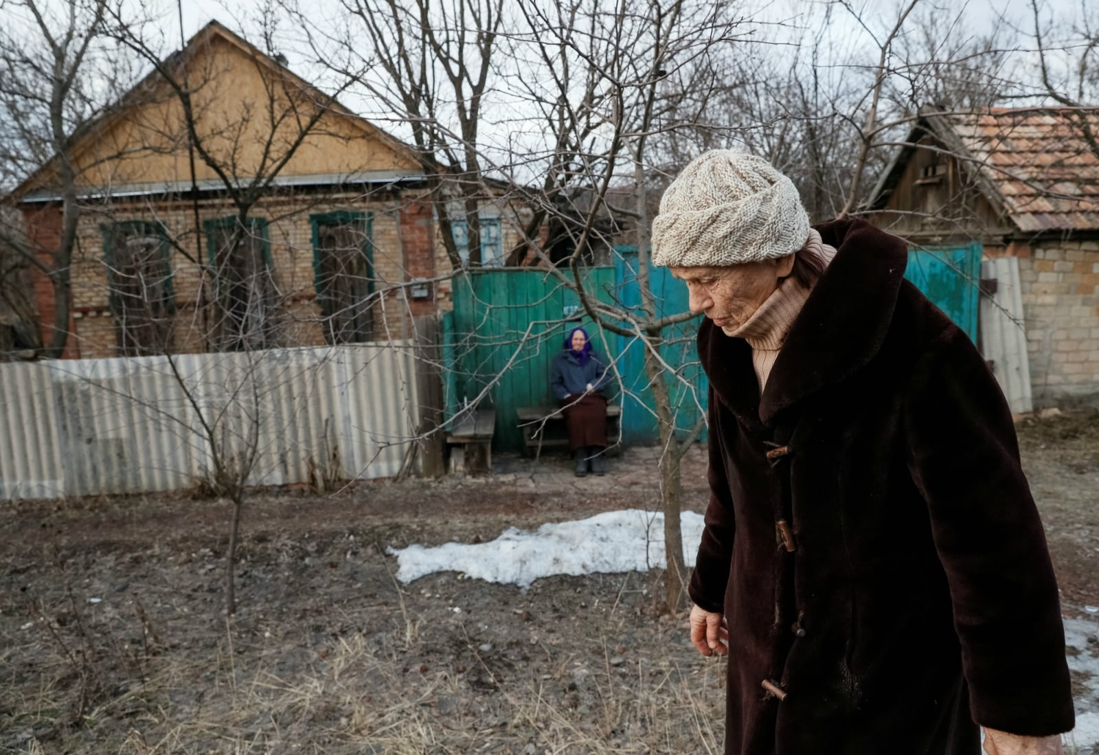 A woman sits outside her house as windows are covered with wood to protect from shrapnel near the front line in the village of Zaitseve, Ukraine, February 23, 2019. There are not many people left in Zaitseve, a village on the front line that divides Ukraine between government-controlled territory and the enclave controlled by Russian-backed separatist forces. Troops are stationed in trenches outside Zaitseve and government trucks risk rebel fire to bring bread, coal, firewood and other goods along a dirt road. REUTERS/Gleb Garanich
