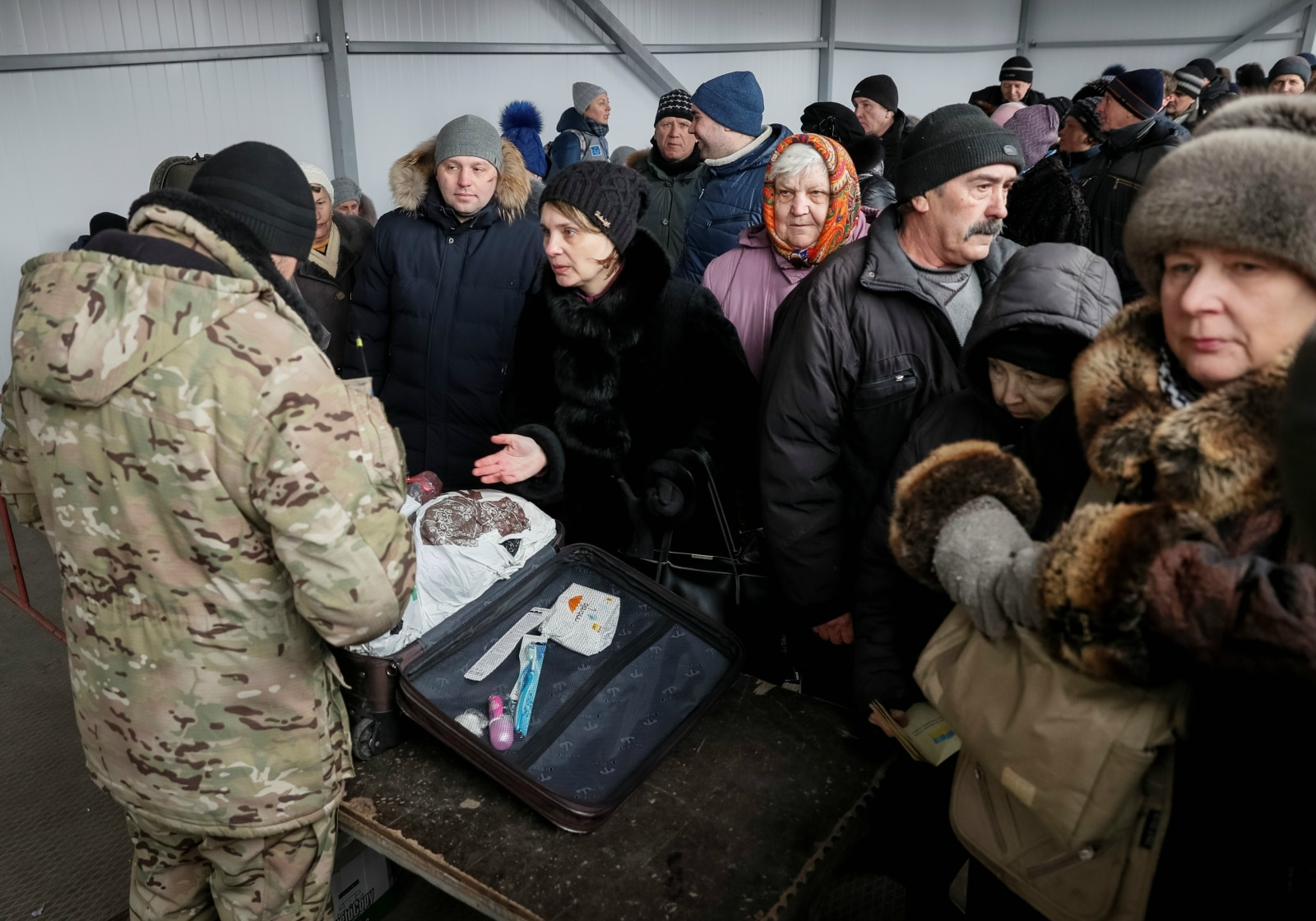 People line up as border guards check their luggage before they go through passport control, after crossing the contact line between pro-Russian rebels and Ukrainian troops in Mayorsk, Ukraine, February 25, 2019. More than a million people cross the 500 km contact line every year, many of them are pensioners who spend hours queuing, in cold, heat, rain or snow, as they rely on state benefits that can only be obtained on the government-controlled side. REUTERS/Gleb Garanich