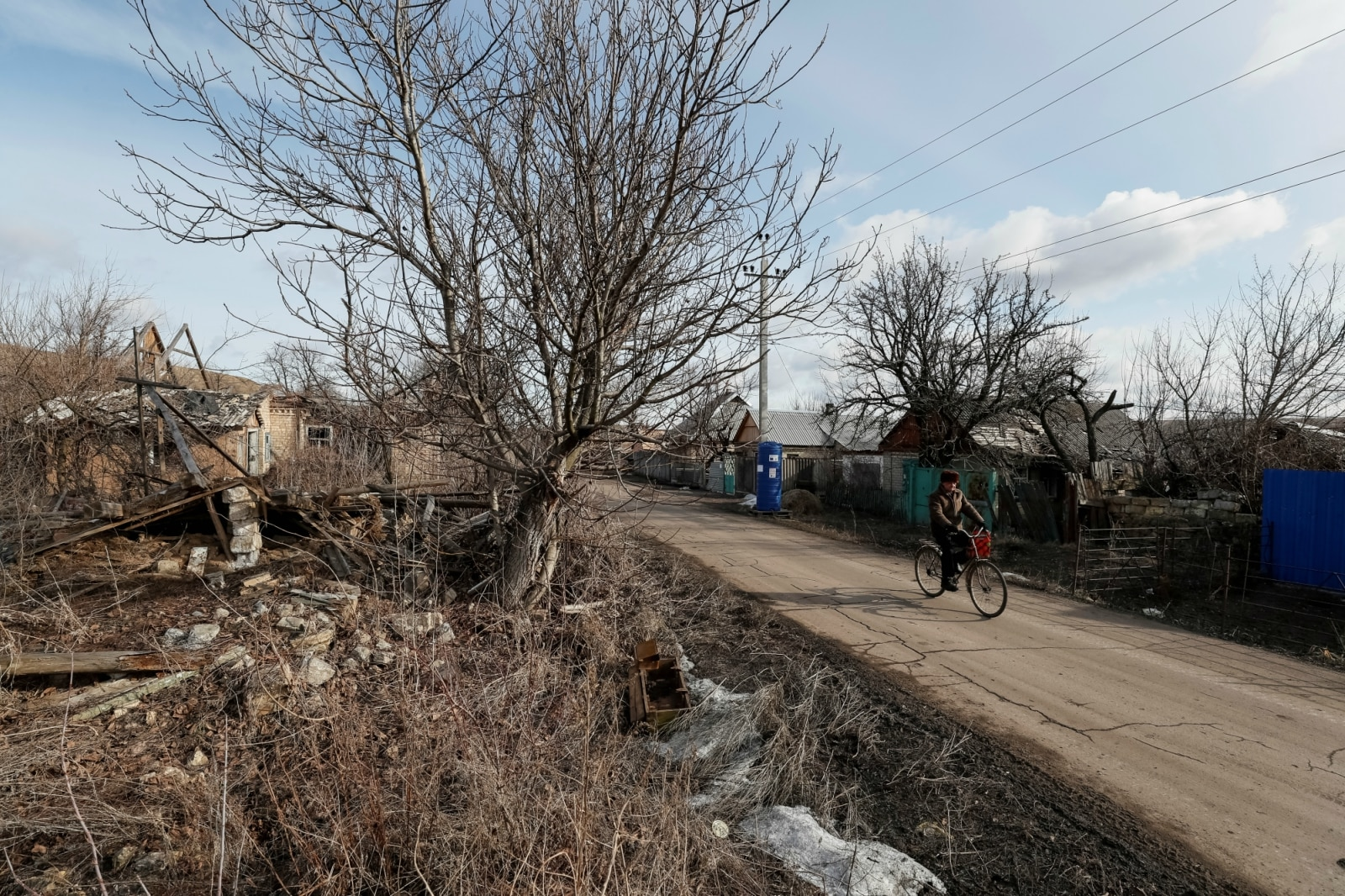 A local resident rides a bicycle past the houses destroyed by shelling in the village of Zaitseve, Ukraine, February 22, 2019. There are not many people left in Zaitseve, a village on the front line that divides Ukraine between government-controlled territory and the enclave controlled by Russian-backed separatist forces. Troops are stationed in trenches outside Zaitseve and government trucks risk rebel fire to bring bread, coal, firewood and other goods along a dirt road. REUTERS/Gleb Garanich