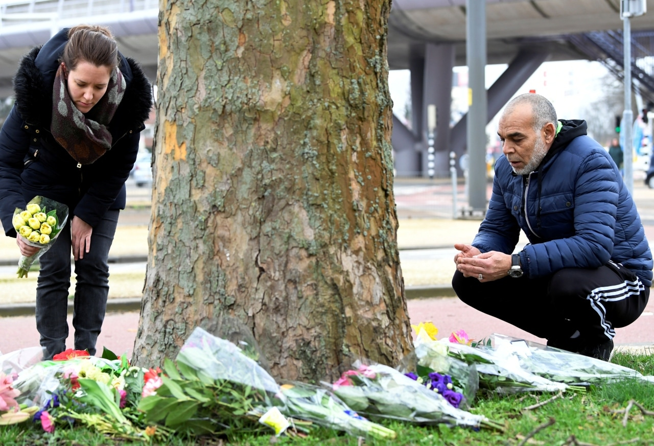 People place flowers at the site of a shooting in Utrecht, the Netherlands March 19, 2019. REUTERS/Piroschka van de Wouw