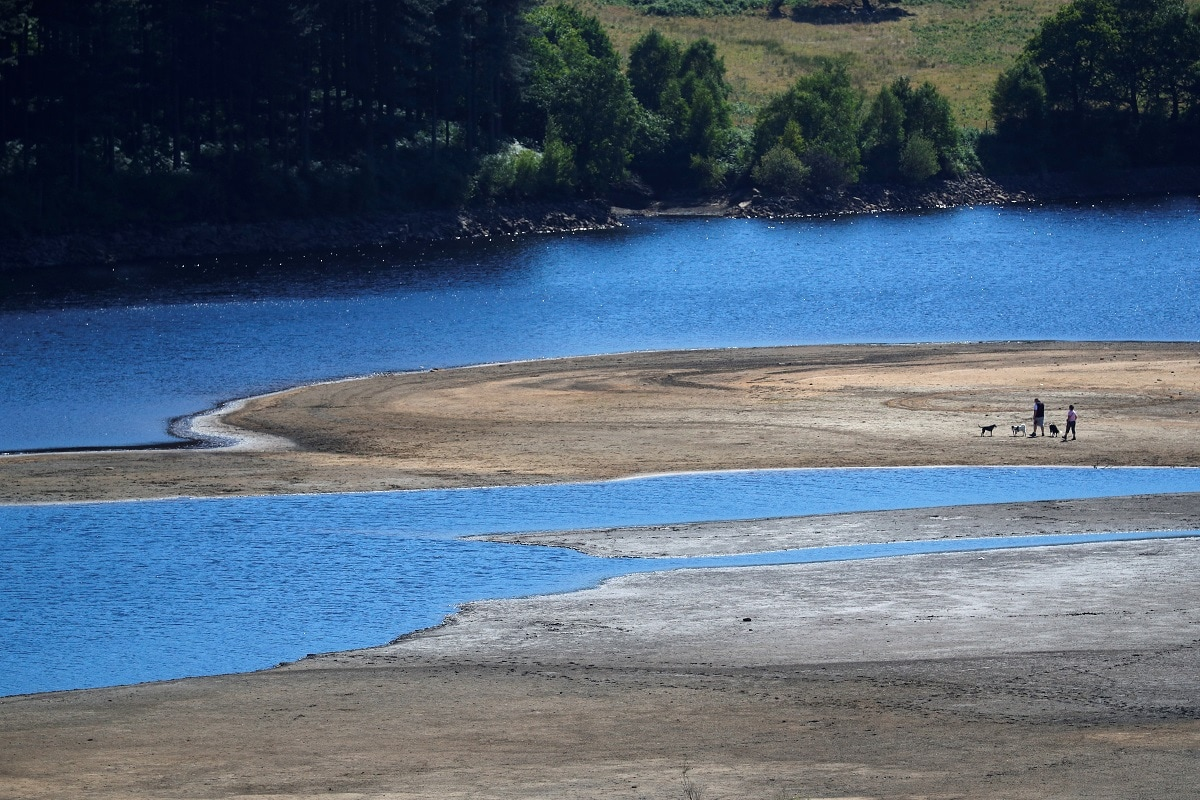 Two people take a walk near the water's edge, where the water level has dropped significantly during the UK heatwave, of Torside Reservoir in Longdendale, Derbyshire, Britain. (REUTERS/Phil Noble)