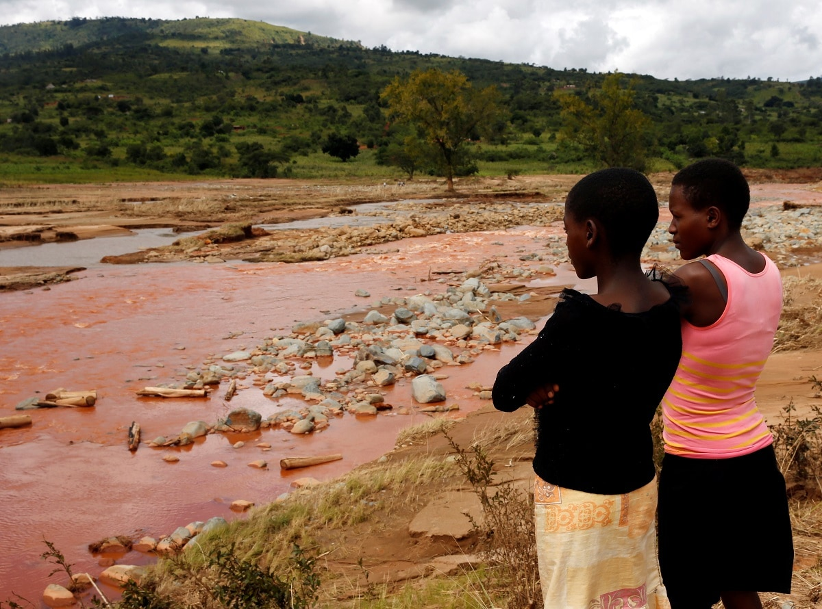 Survivors look at the site of a bridge that was washed away by Cyclone Idai at Peacock Growth Point in Chimanimani, Zimbabwe. (REUTERS/Philimon Bulawayo)