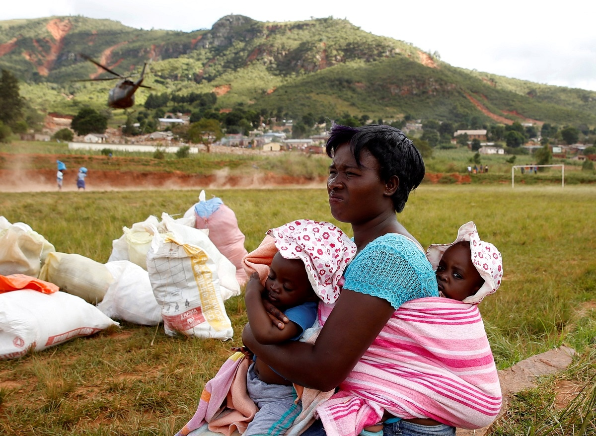 A woman carrying children looks away as a helicopter throws up dust as it takes off after delivering food aid at Ngangu in Chimanimani, Zimbabwe. (REUTERS/Philimon Bulawayo TPX IMAGES OF THE DAY)