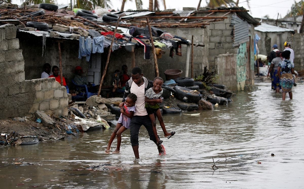 A man carries his children after Cyclone Idai at Praia Nova, in Beira, Mozambique. (REUTERS/Siphiwe Sibeko TPX IMAGES OF THE DAY)