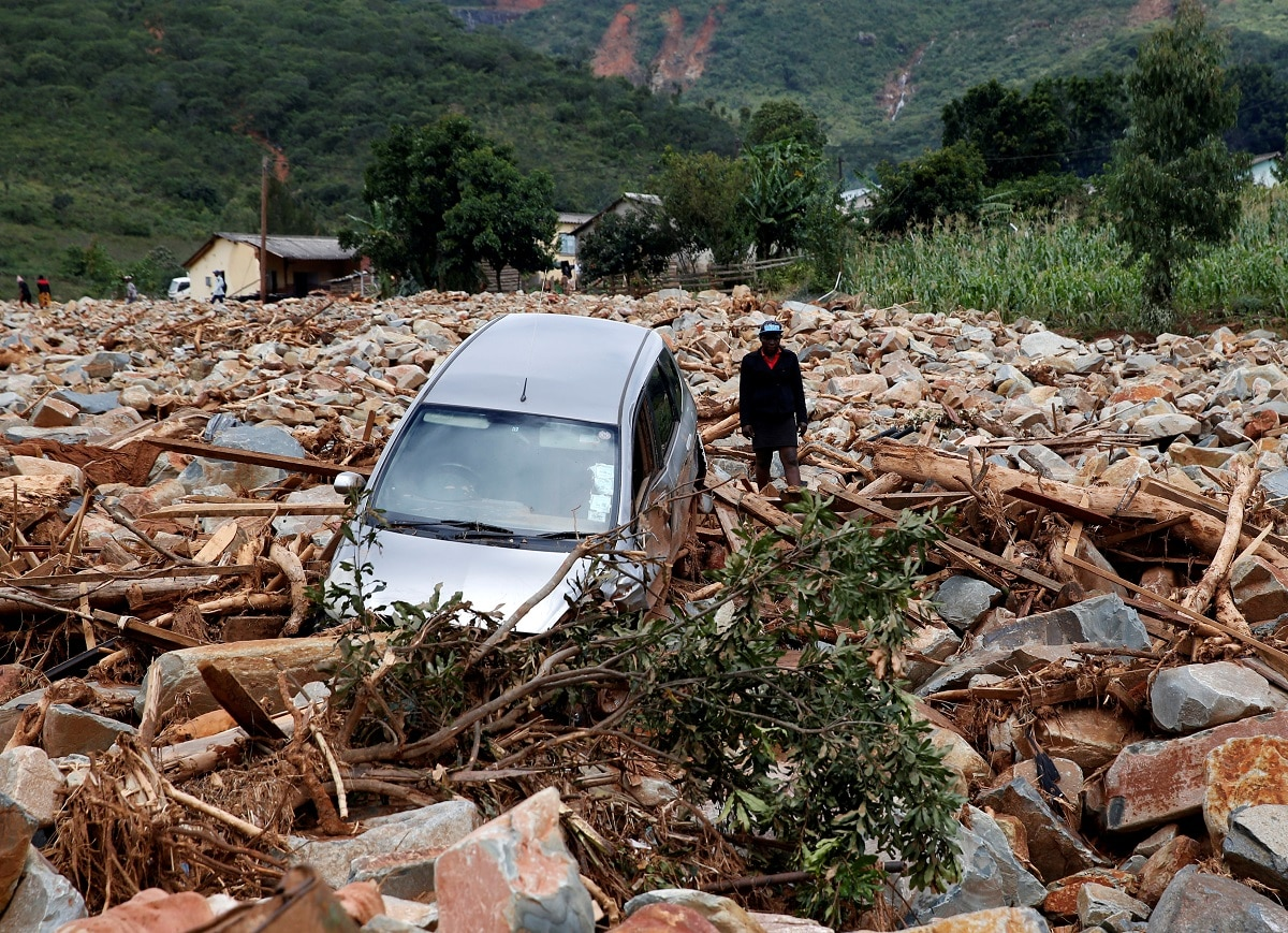 A woman stands beside a car that was swept away with debris by Cyclone Idai in Chimanimani, Zimbabwe. (REUTERS/Philimon Bulawayo)